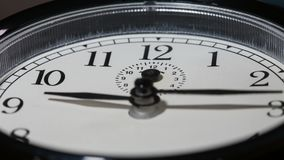 Closeup on slowly rotating clock face with fast moving clock hands stock footage