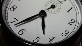 Closeup on slowly rotating clock face with fast moving clock hands - time running out stock video