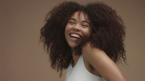Closeup slowmotion portrait of laughin black woman with curly hair. In studio stock video