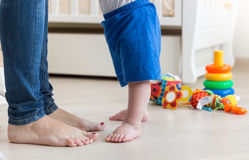 Closeup of small baby`s feet on floor at living room next to mot. Closeup photo of small baby`s feet on floor at living room next to mothers feet Royalty Free Stock Images
