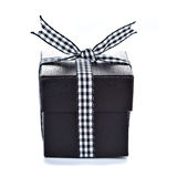 Black gift box with checkered ribbon Stock Images