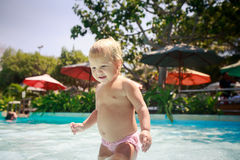 closeup small blonde girl holds pole in shallow hotel pool Royalty Free Stock Image