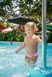 Closeup small blonde girl holds pole in shallow hotel pool Stock Photo