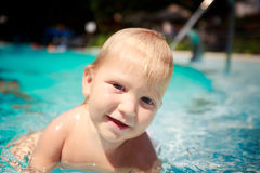 closeup small blonde girl smiles looks into camera in hotel pool Royalty Free Stock Photography