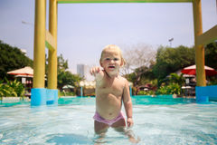 Closeup small blonde girl stands in pool water points towards Stock Images