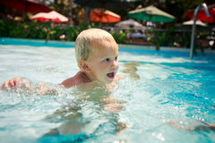 Closeup small blonde girl stands in shallow hotel swimming pool Stock Photography