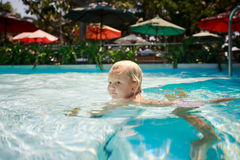 Closeup small blonde girl swims in shallow hotel swimming pool Stock Photo