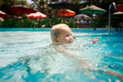 Closeup small blonde girl swims smiles in hotel swimming pool Royalty Free Stock Photo