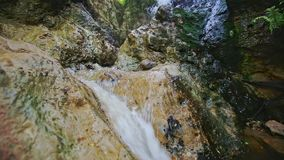Closeup Small Foamy Mountain Waterfall Flows into River stock footage