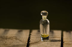 Closeup small glass bottle for magicians with tiny amount of remedy inside, standing on wooden surface.  Stock Photo