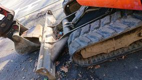 Small Mini Hydraulic Excavator Digger. Closeup of Small Mini Hydraulic Excavator Digger with rubber tracks and buckets stock images