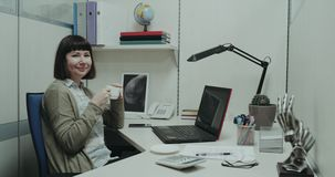 Closeup in the small office corner young woman take a break at her desk drinking coffee and smiling, start to work at. Her notebook stock video footage