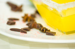 Closeup small pieces of dark chocolate lying on white plate next to transparent square bowl sugarcoated with yellow Royalty Free Stock Photography