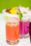 Closeup small sugarcoated shotglasses with delicious orange and purple juices inside Stock Photography