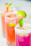 Closeup small sugarcoated shotglasses with delicious orange and purple juices inside Royalty Free Stock Image