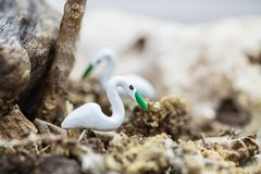 Closeup small wooden white bird for decorate in flowerpot on blurred background. Closeup small wooden white bird for decorating in flowerpot on blurred stock image