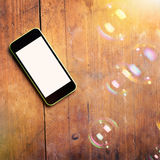 Closeup of smart phone and bubbles on wooden surface Royalty Free Stock Image