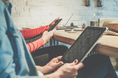 Closeup of smartphone and digital tablet in hands of business women sitting at wooden table in cafe. In background white brick wall.Selective focus,blurred Stock Photo