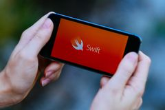 Closeup of smartphone screen with APPLE SWIFT LOGO and ICON