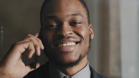 Closeup smiling black business man talking mobile smartphone in office. Close up of cheerful entrepreneur having phone