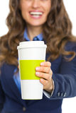 Closeup on smiling business woman giving cup of hot beverage Royalty Free Stock Photos