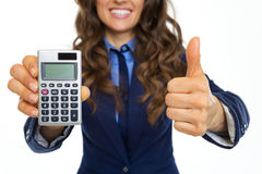 Closeup on smiling business woman showing calculator and thumbs Stock Photography