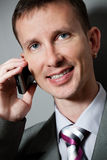 Closeup smiling businessman with phone. Over gray Stock Photo