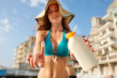 Closeup of smiling caucasian woman showing sunscreen oil bottle and using sun protection cream smear on finger. Pretty stock photos