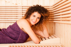 Closeup of smiling curly woman in wooden sauna Royalty Free Stock Photography