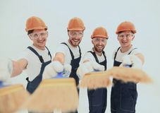 Smiling group of builders with a paint brush. Closeup.smiling group of builders with a paint brush.isolated on white stock photos