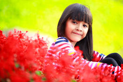 Closeup smiling little asian girl sitting on flower field Royalty Free Stock Image