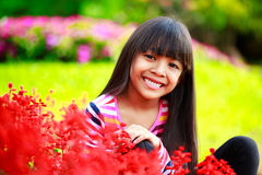Closeup smiling little asian girl sitting on flower field Stock Images
