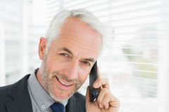 Closeup of smiling mature businessman using cellphone Stock Images