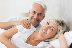 Closeup of a smiling mature couple lying in bed Stock Images