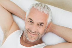 Closeup of a smiling mature man resting in bed Royalty Free Stock Image