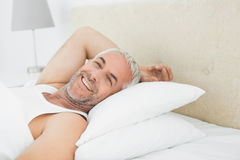 Closeup of a smiling mature man resting in bed Royalty Free Stock Photo