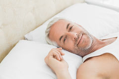 Closeup of a smiling mature man resting in bed Stock Photography