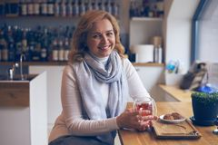 Smiling mature woman posing at camera in cafe Stock Photo