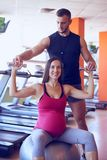 Smiling pregnant woman exercising in gym with personal trainer Stock Photography