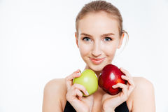 Closeup of smiling pretty sportswoman with green and red apples. Closeup of smiling pretty young sportswoman with green and red apples over white background royalty free stock photos