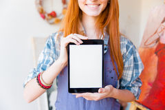 Closeup of smiling pretty woman artist showing blank screen tablet Stock Photos