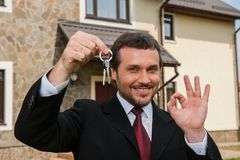 Closeup on smiling real estate agent ready to sell house. Male real etate agent in front of home holding keys and ok sign Stock Image