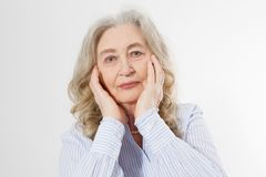 Closeup of smiling senior woman wrinkle face and gray hair. Old mature lady touching her wrinkled skin  on white. Background. Copy space royalty free stock photo