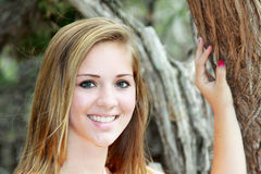 Closeup smiling teen girl with hand on a tree. Closeup of a smiling teen girl with clear skin and straight teeth standing outside with her hand on a tree royalty free stock images