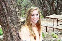 Smiling teen girl leaning on a tree. Closeup of a smiling teen girl with clear skin and straight teeth standing outside leaning on a tree royalty free stock photo