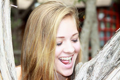 Smiling teen girl with eyes closed. Closeup of a smiling blonde teen girls face with eyes closed between two trees Stock Photos