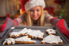 Closeup on smiling teenage girl pulling out pan of fresh cookies Royalty Free Stock Images
