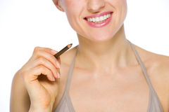 Closeup on smiling woman holding brown eye liner Royalty Free Stock Photos