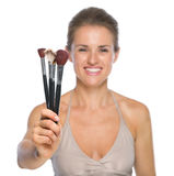 Closeup on smiling woman showing makeup brushes Stock Photography