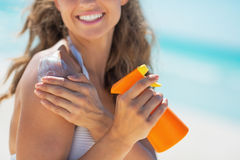 Closeup on smiling woman with sun screen creme. Closeup on smiling young woman with sun screen creme Royalty Free Stock Photography